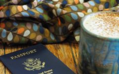 A picture of my first United States Passport with an almond milk latte in a ceramic mug beside it and a scarf with softly colored stylistic leaves on it in the background