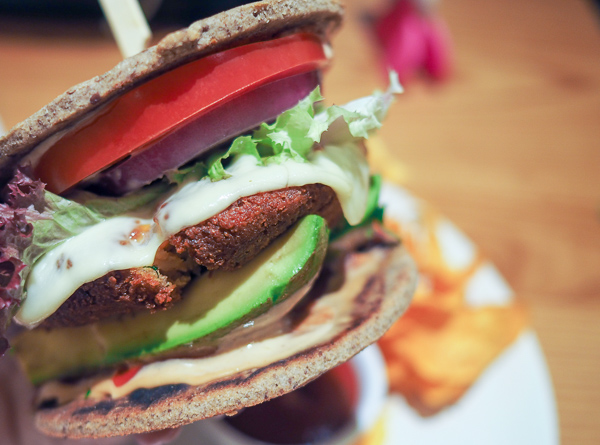 "Picture shows Avocado Restaurant's Signature Veggie Burger, loaded with avocado, slices of tomato, lettuce, and quinoa black bean patty topped with cheese on a sprouted flatbread ""bun"") and a side of sweet potato chips"