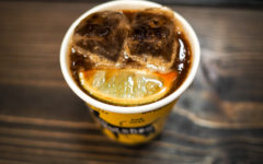 Image shows a cup of Underdog Project's Famous Iced Coffee Tonic - Espresso Over Ice, Topped with Tonic and a Fresh Lime Wedge