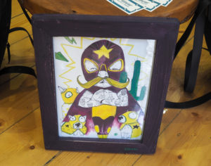 Picture shows an illustration called The Wrestler by Little Rocks Design. It is a wrestler with tattooed arms in a yellow and purple leotard, a purple cape and tights, a big yellow handlebar mustache, and a purple full face mask with yellow star on the forehead. Surrounding him are three bull terriers wearing miniature yellow masks and costumes to match the wrestler.