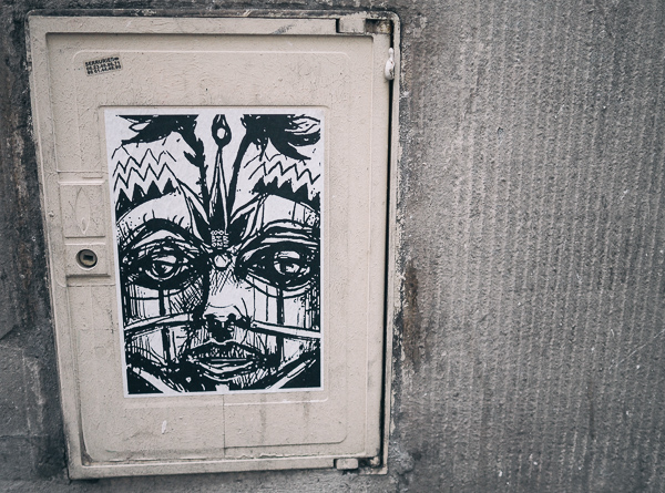 Street art in Paris showing a black and white image of an African warrior in ceremonial face makeup and jewelry, including nose bone.