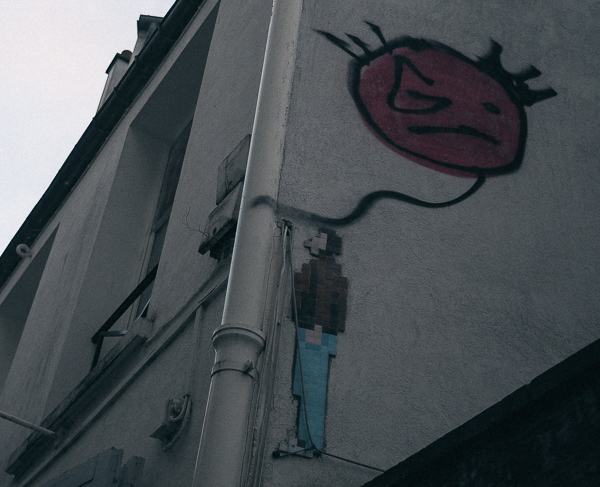 Paris street art of man looking up at a red balloon
