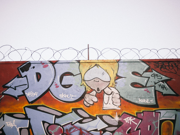Mural of block letters with a blonde cartoon character with huge white sunglasses covering his upper face - in Montmartre by Street Artist Skout of TPK Crew - Paris Street Art