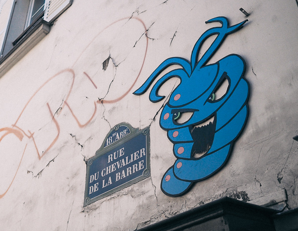 Paris Street Art in Montmarte's Sacre Couer Neighborhood showing 3D blue creature with big eyes and toothy open mouth that resembles a cross between a worm and a turnip