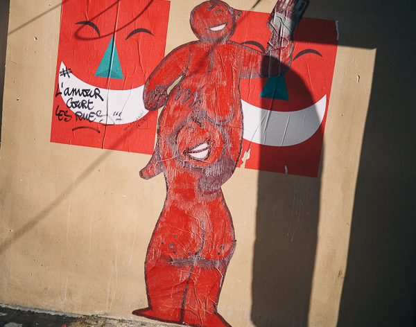 Paris Street Art 2017 - Artist Unknown - image shows one red cartoon character letting another stand on their shoulders in order to paste up two posters showing large red faces with big white grins