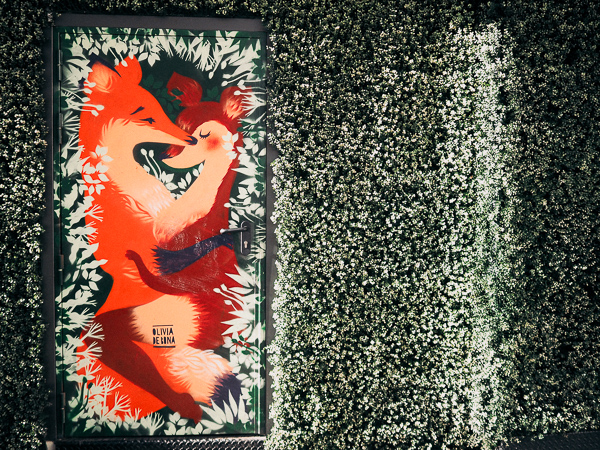 Whimsical and Textural Paris Street Art by Artist Olivia de Bona of 9e Concept. Wall surrounding door is covered in faux plastic grass and flowers and on the door is painted two foxes snuggling discreetly in the grass.