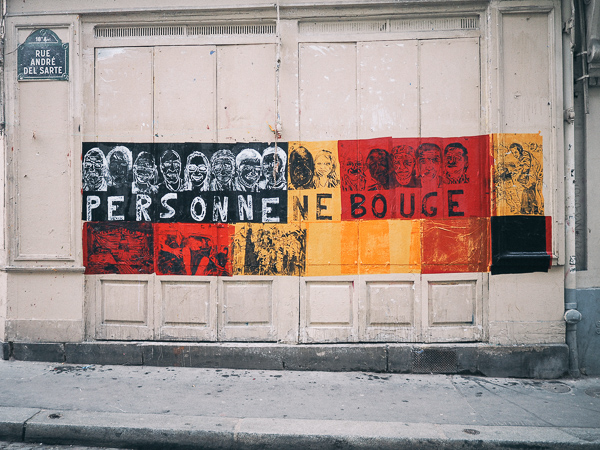 "A large street art piece that says Personne Ne Bouge and has faces drawn above each letter. This translates to ""Nobody Moves"""