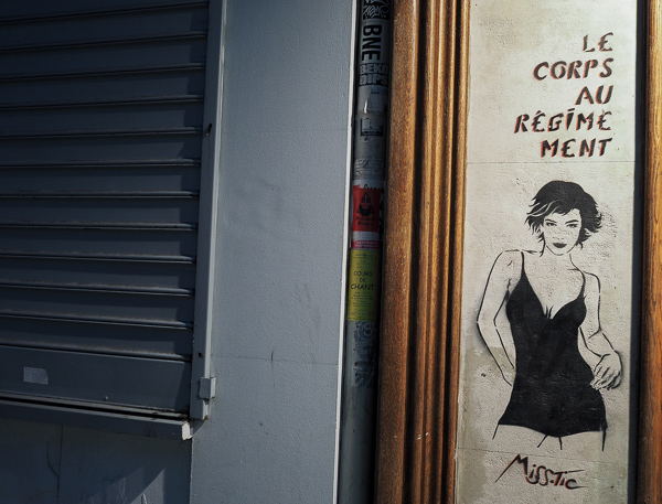 "Paris street art showing a thin woman in a short and tight black dress with the text above ""Le corps au régimement"" which loosely translated she implies ""the body on diet lies"""
