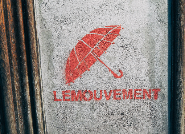 "Paris Street Art featuring a stencil of an umbrella and below it the text ""Lemouvement"" , meaning movement"