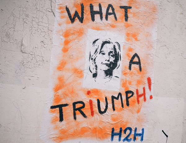 "Trump - Hillary Political Paris Street Art showing a picture of Hillary and words around it saying ""What a Triumph!"" with the i and h in a different color so that only TRUMP reads clearly."