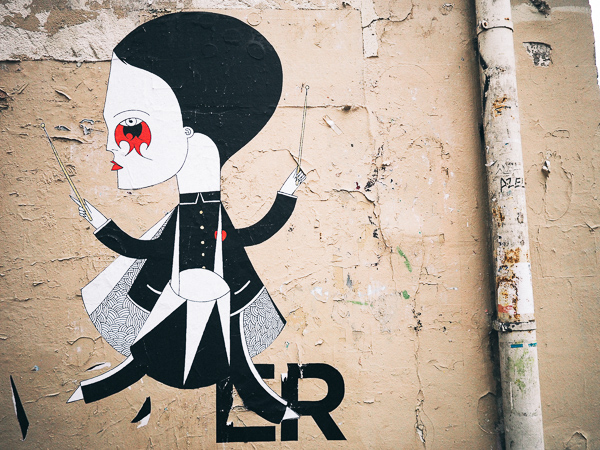 Paris street art by French artist Fred le Chevalier that shows a highly stylized male figure with an oversized head and red makeup design under the figure's eye.