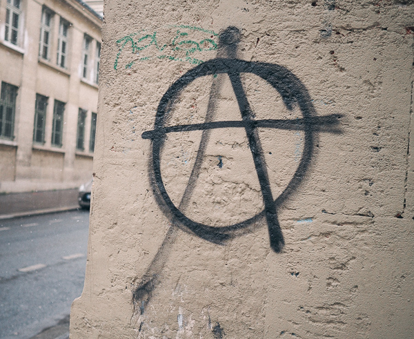 A spray painted anarchy symbol on a side street in Paris