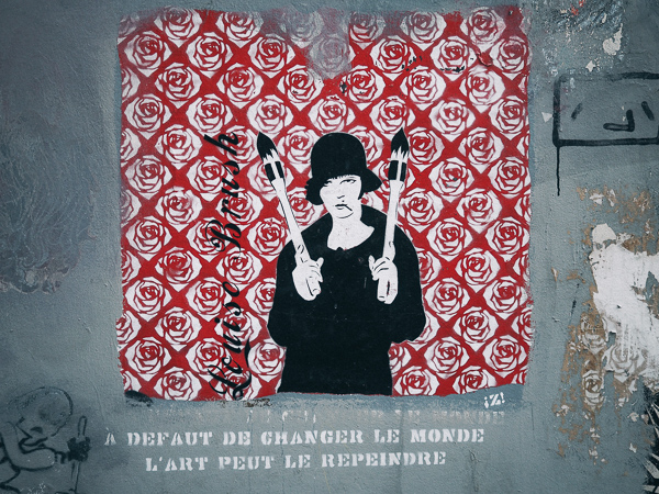 "A suffrage woman with grenades in her hands over a red rose like background, below her the words - ""a defaut de changer le monde l'art peut le repeindre"" which means roughly thathaving failed to change the world, art can repaint it."