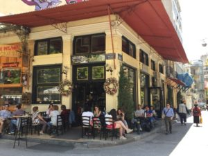 exterior photo of Nancy's Sweet Home pastry and cake shop in Athens Greece. Picture shows people sitting at cafe tables out front and on the side of the corner bakery. Photo taken by Janao of Norway.