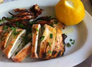 Photo showing grilled calamari with parsley and lemon at Parodosiako Tavern in Athens Greece