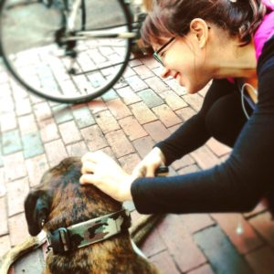 Amanda Phillips bent down and happilly petting Ronin the Boxer dog in Davis Square, summer of 2015